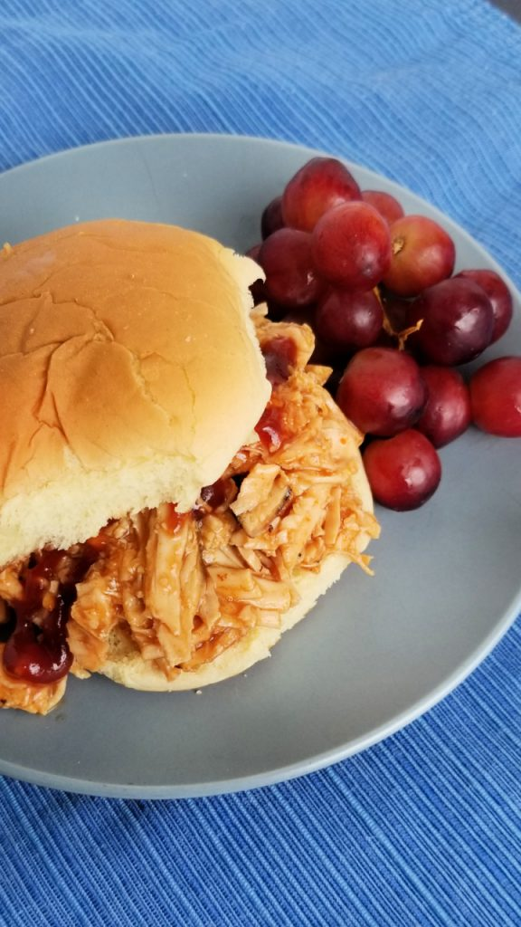 A sandwich with slow cooker bbq chicken with grapes on a plate.