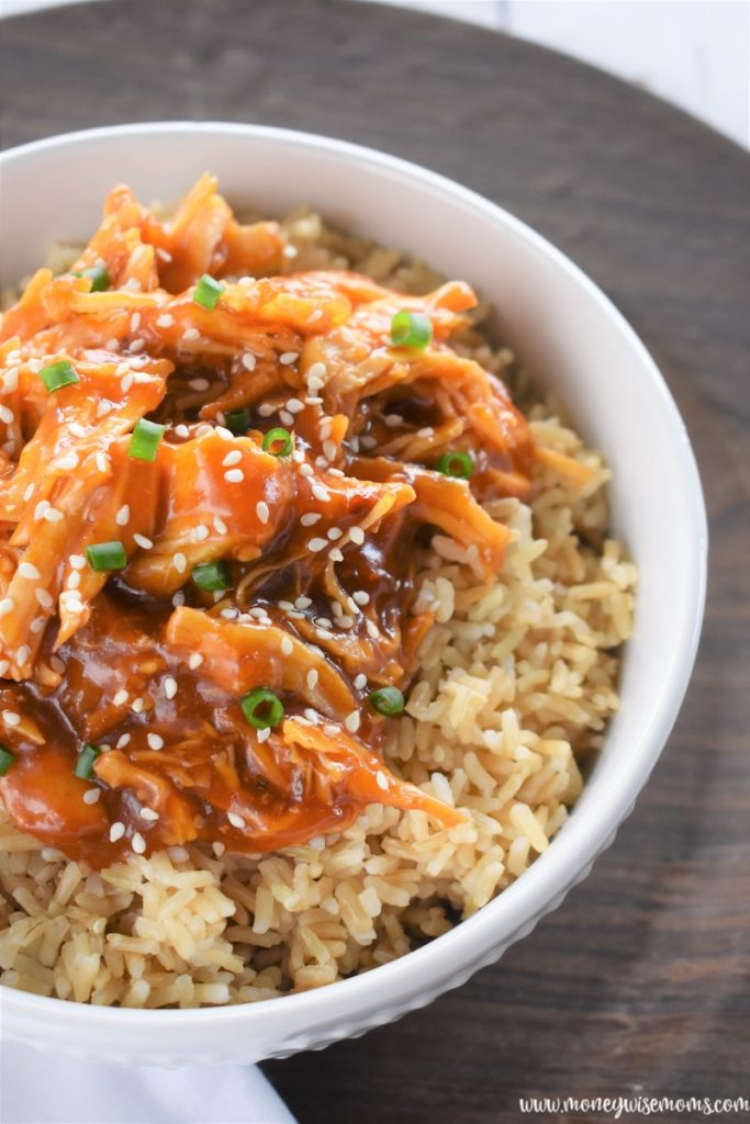 A bowl of brown rice with chicken teriyaki on top.