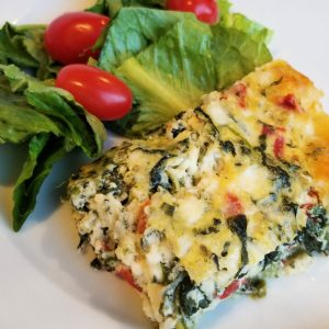 Piece of Italian spinach pie on white plate with green salad and tomatoes