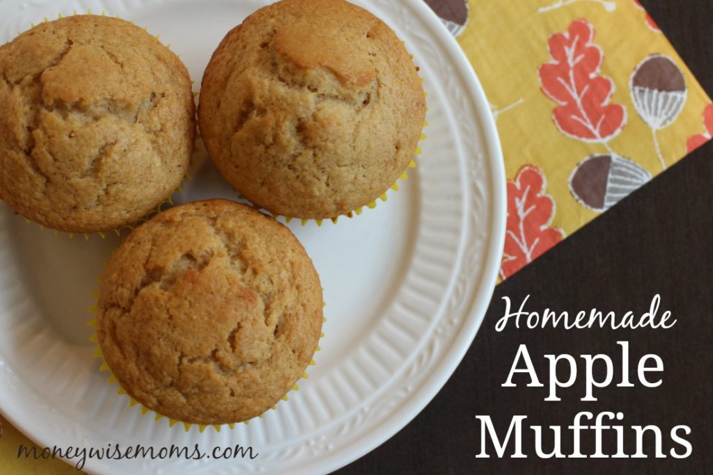 three homemade apple muffins on white plate with gold napkin