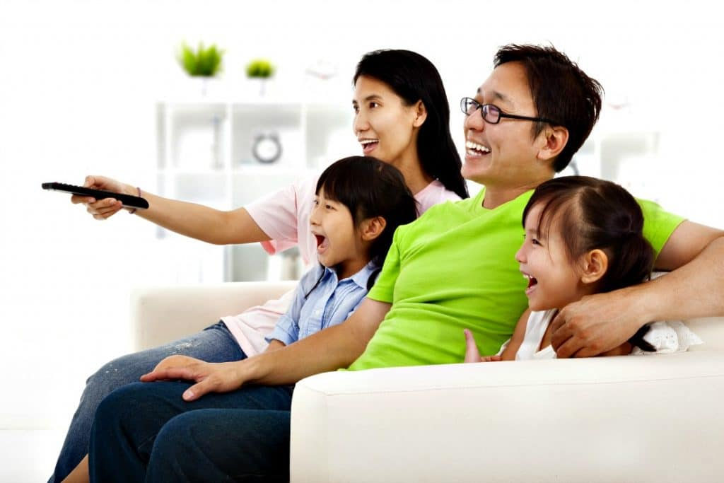 family watching TV together - family movie night ideas