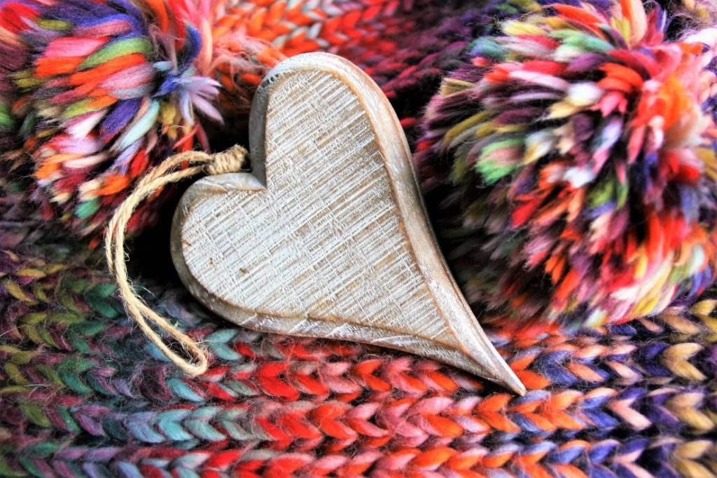 Handmade wooden heart ornament on winter knits