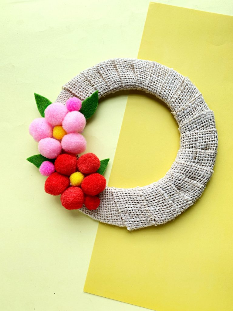 This beautiful pom pom wreath makes a great Mother's Day gift. It's a cute, DIY project you can make at home with very little in materials or cost. This is a simple Mother's Day wreath that you can customize!