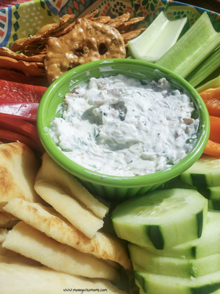 A view of the finished dip on a tray full of veggies and crackers.