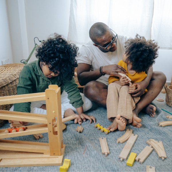 African American man playing with kids at home