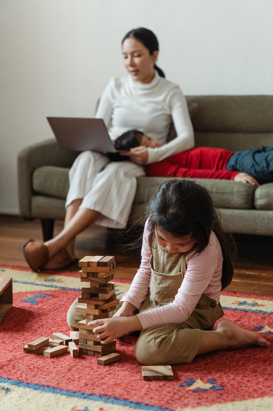A mom with laptop sitting on couch with daughter on the floor playing 0 work from home with kids