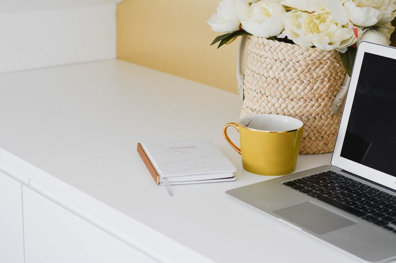 Yellow mug next to laptop on a clean desk