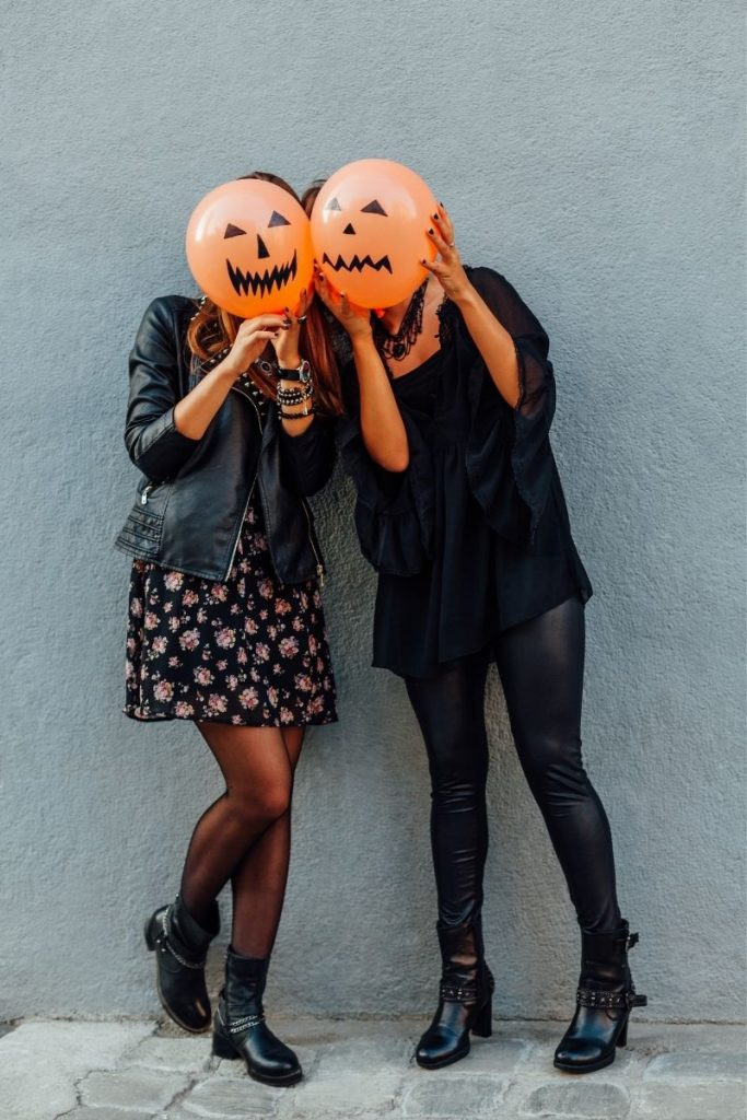 Teen girls wearing black and holding jack o lantern balloons - halloween costumes for teens
