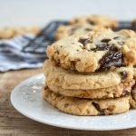 Stack of walnut chocolate chunk cookies on white plate