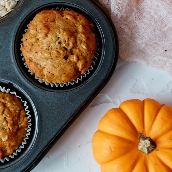Pumpkin Oatmeal Muffins in muffin pan with mini pumpkin