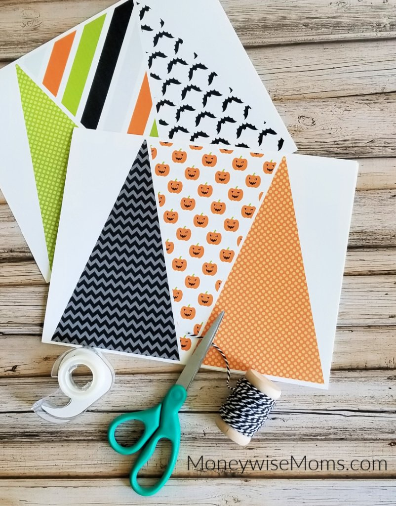 paper flags string tape and scissors to make Halloween bunting