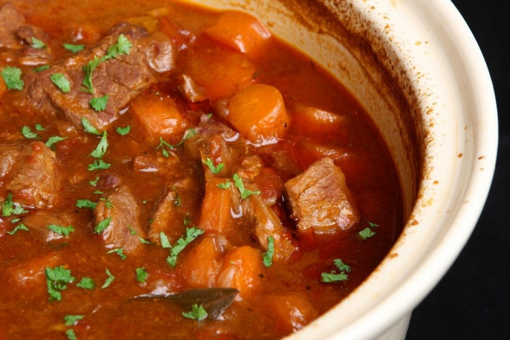 Beef and vegetable soup in white crock - crockpot soup recipes