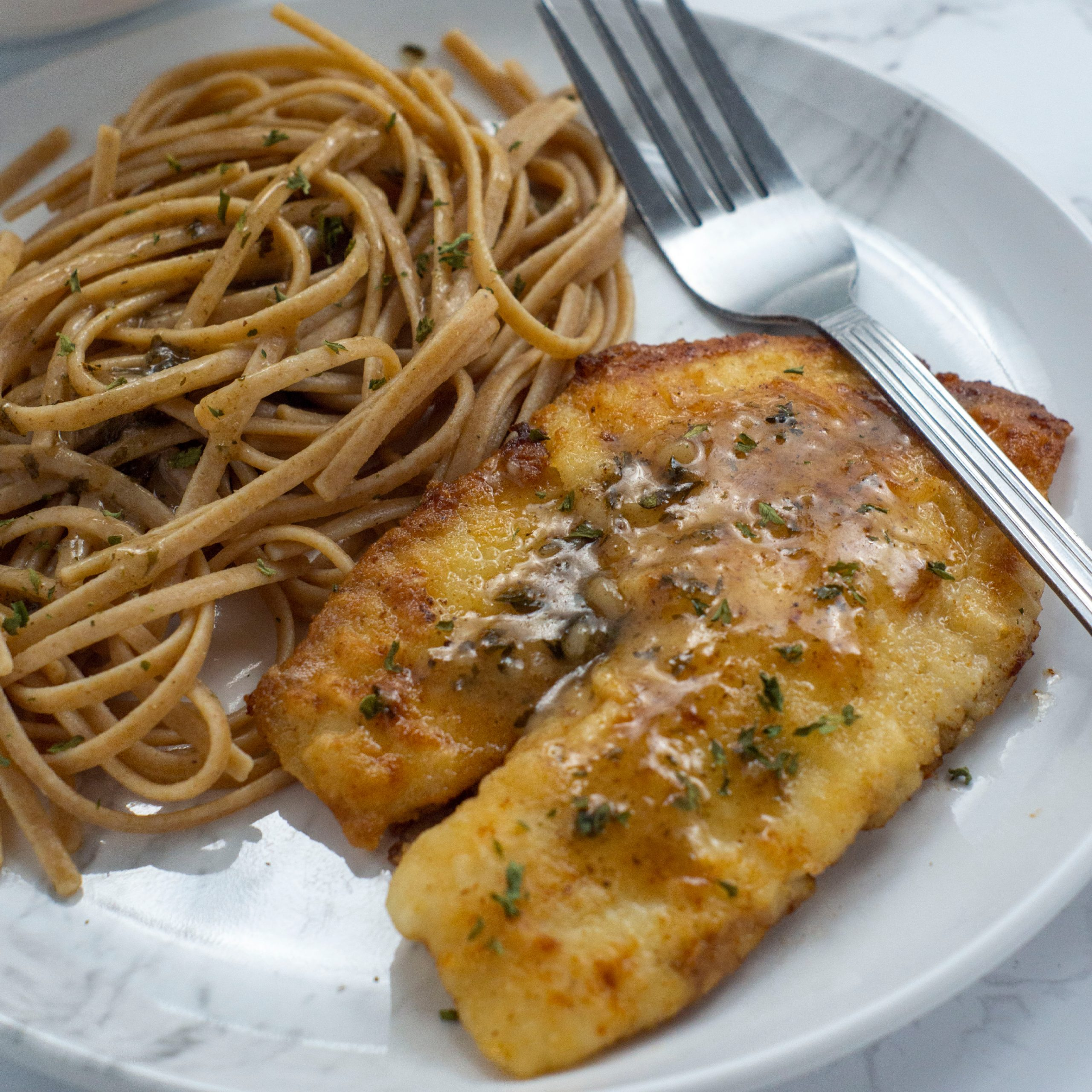 Lemon butter tilapia filet and noodles on white plate
