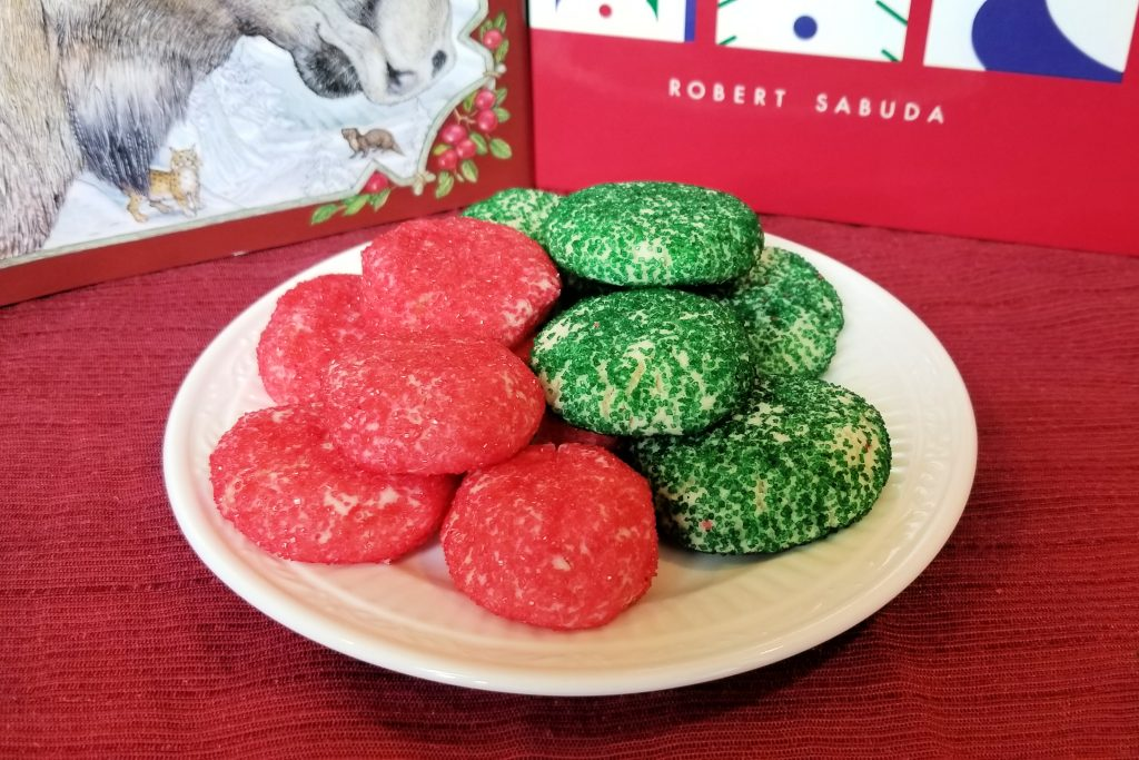 White plate with green and red sugar sprinkle cookies in front of Christmas books