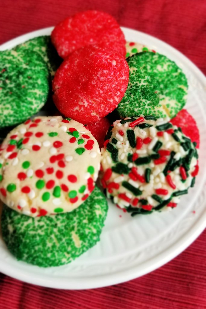 Green red and multicolored sprinkles on sugar cookies on white plate on red placemat
