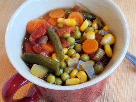 Vegetable soup in a red mug with handle