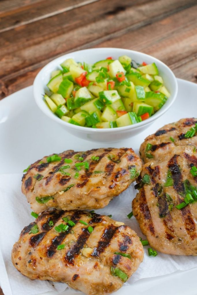 Turkey burgers with cucumber salad on white plate