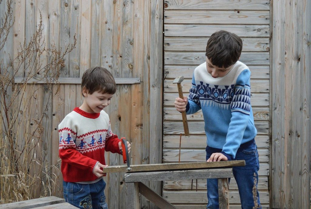 Two boys with clamp hammer and wood doing open buildilng