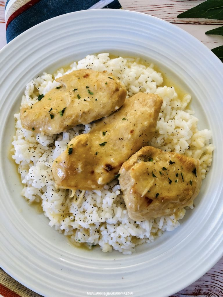 A look from the top down at the finished slow cooker lemon pepper chicken served in a white bowl over a bed of rice.