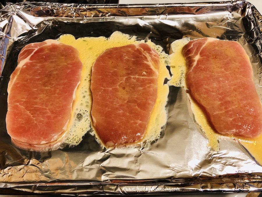 Prepared baking sheet with cooking pork chops on top.