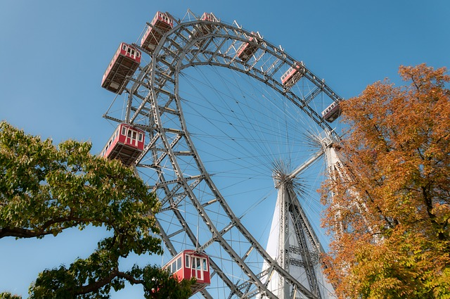 Ferris wheel with red cars against blue sky and fall trees - theme park military appreciation days