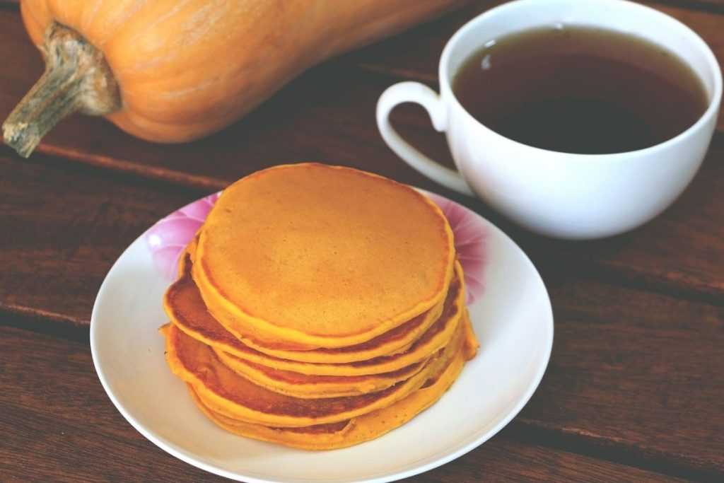 Stack of pumpkin pancakes on white plate with cup of coffee - pumpkin pancakes easy