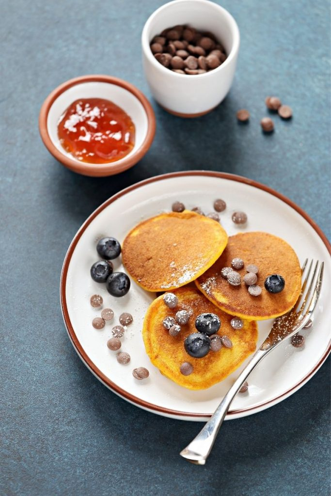 pumpkin pancakes on white plate with chocolate chips - recipe for pumpkin pancakes