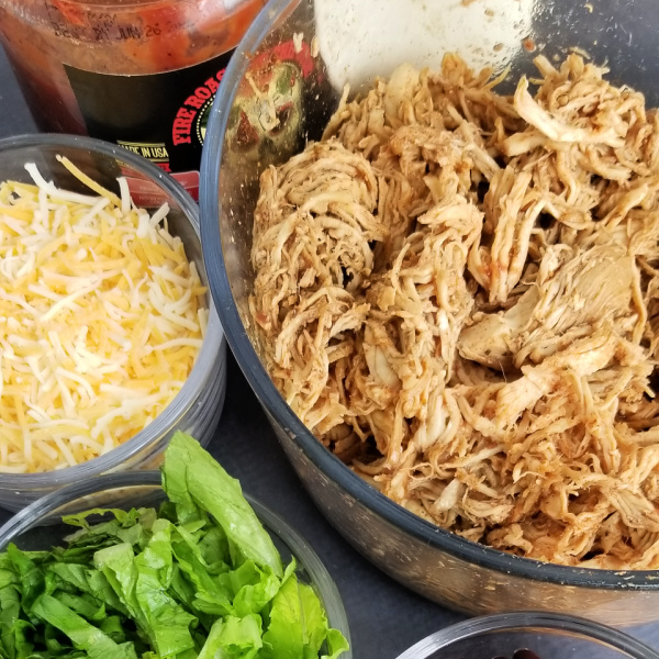 Shredded chicken taco meat with shredded cheese and lettuce in bowls - beginner slow cooker meals