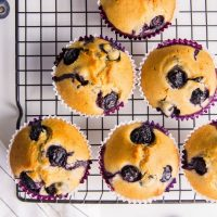 blueberry muffins on cooling rack on marble countertop