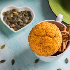 pumpkin wheat muffin in white mug next to bowl of pumpkin seeds