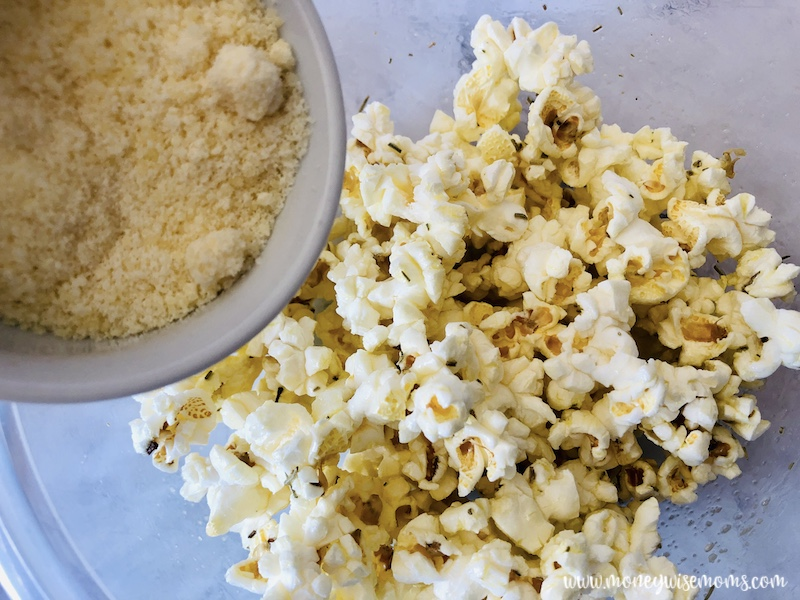 Parmesan cheese being added to the popcorn.