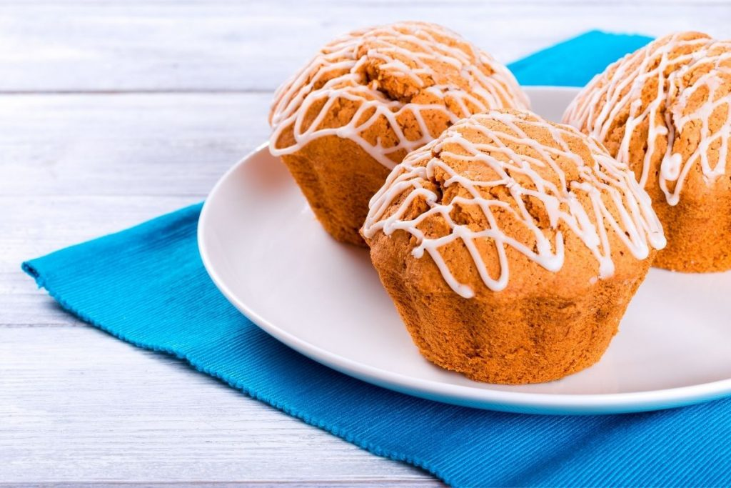 Vanilla wheat muffins on white plate on blue placemat on wooden table