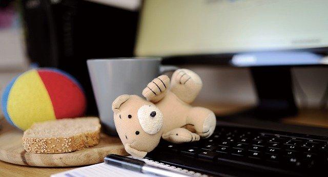 computer keyboard with teddy bear piece of bread mug and ball