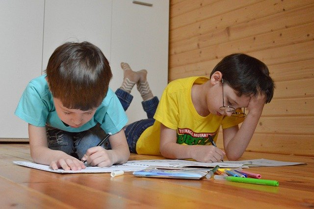 Two boys lying on floor coloring