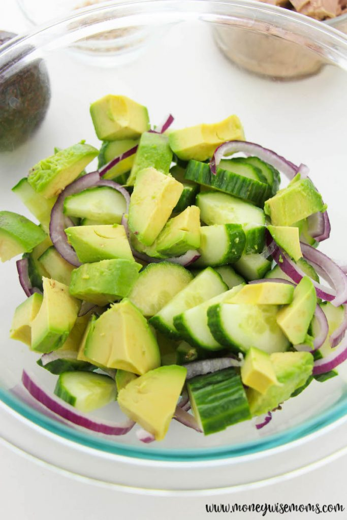 avocado added to the bowl of sliced cucumbers and onions.