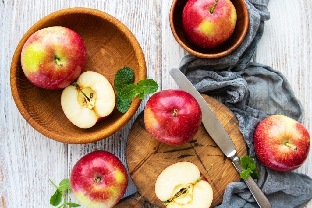 Whole and halved apples in wooden bowl - apple recipes for dessert