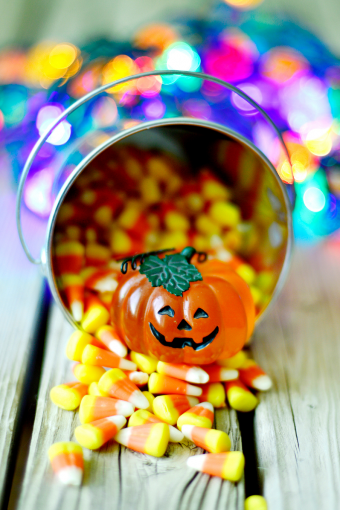 Metal bucket spillout out candy corn with plastic Jack o Lantern - family Halloween