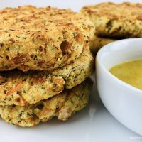 Finished easy recipe for salmon patties next to dill mustard dipping sauce.