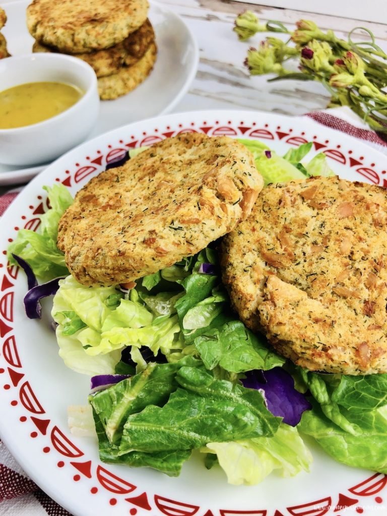 patties on a bed of greens without sauce ready to eat.