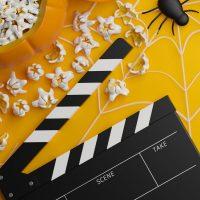 movie clapboard with popcorn and spider on orange background