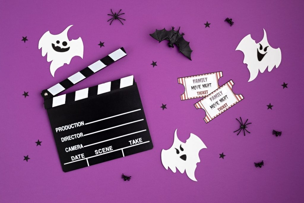Family movie night tickets with Hollywood clapboard and ghosts on purple background