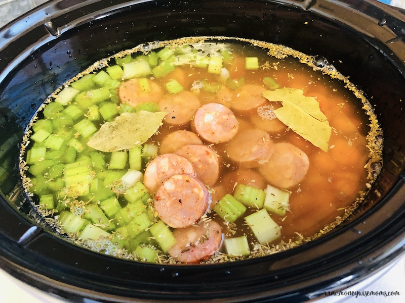 sausage and veggies added to the broth in the crockpot.