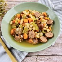 Featured image showing a bowl full of the finished sausage and bean slow cooker soup.
