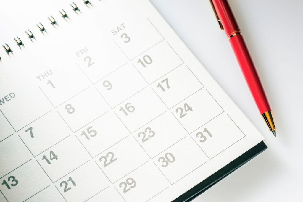 Black and white calendar with red pen on white surface - Medicare open enrollment